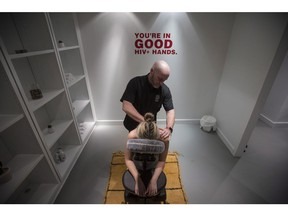 Randy Davis, who is HIV-positive, demonstrates a head, neck and shoulder massage on Jackie Kleinberg at the Healing House, the world's first pop-up HIV+ spa in Toronto on Thursday, Nov. 29, 2018.