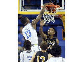 UCLA guard Kris Wilkes, left, dunks the ball over Fort Wayne forward Cameron Benford, right, during the first half of an NCAA college basketball game Tuesday, Nov. 6, 2018, in Los Angeles.