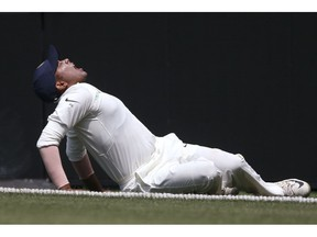 India's Prithvi Shaw grimaces as he falls to the ground after rolling his ankle while attempting a catch during their tour cricket match against Cricket Australia XI in Sydney, Friday, Nov. 30, 2018.