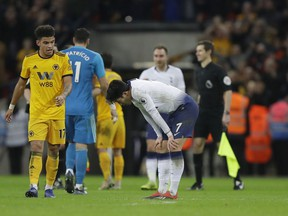 Tottenham Hotspur's Son Heung-min, bends down after the end of the English Premier League soccer match between Tottenham Hotspur and Wolverhampton Wanderers, as Wolverhampton Wanderers Morgan Gibbs-White walks past at Wembley stadium in London, Saturday, Dec. 29, 2018. Wolves won the game 3-1.