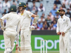 Australia's Nathan Lyon, left, and Pat Cummins, center, at the end of an over speak as India's Virat Kohli looks on during play on day five of the third cricket test between India and Australia in Melbourne, Australia, Sunday, Dec. 30, 2018.