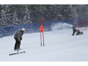 Workers prepare the course as it snows before a scheduled Men's World Cup super-G skiing race Saturday, Dec. 1, 2018, in Beaver Creek, Colo.
