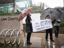Supporters hold a sign outside B.C. Supreme Court during the third day of a bail hearing for Meng Wanzhou, the chief financial officer of Huawei Technologies, in Vancouver, on Dec. 11, 2018.