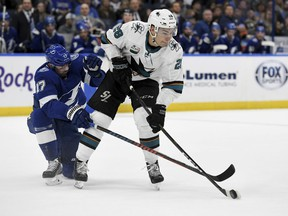 Tampa Bay Lightning left wing Alex Killorn (17) and San Jose Sharks right wing Timo Meier (28) fight for the puck during the first period of an NHL hockey game Saturday, Jan. 19, 2019, in Tampa, Fla.