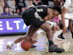 Wake Forest forward Jaylen Hoard (10) and Georgia Tech guard Brandon Alston (4) battle for a loose ball during the first half of an NCAA college basketball game, Saturday, Jan. 5, 2019, in Atlanta.
