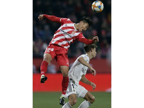 Real Madrid's Marcos Llorente, right, duels for the ball with Girona's Paik Seung-ho during a Spanish Copa del Rey soccer match between Girona and Real Madrid at the Montilivi stadium in Girona, Spain, Thursday, Jan. 31, 2019.