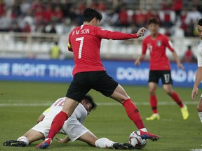 China's defender Zheng Zhi, ground, and South Korea's forward Son Heung-Min fight for the ball during the AFC Asian Cup group C soccer match between South Korea and China at Al Nahyan Stadium in Abu Dhabi, United Arab Emirates, Wednesday, Jan. 16, 2019.
