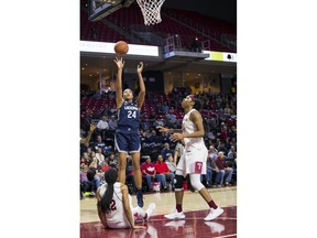 Connecticut's Napheesa Collier, center, shoots the ball with Temple's Emani Mayo, left, and Shantay Taylor, right, defending during the first half of an NCAA college basketball game, Saturday, Jan. 19, 2019, in Philadelphia.