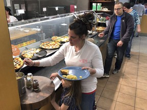 U.S. Coast Guard spouse Rachel Malcom, left, gathers food for herself and her daughter, Tuesday, Jan. 15, 2019, at Roger Williams University in Bristol, R.I. The college offered a free dinner for active-duty Coast Guard members and their families in Rhode Island and southeastern Massachusetts who are working without pay during the partial federal shutdown. The Coast Guard is affected because it's part of the Department of Homeland Security. Other military services receive funding through the Defense Department.