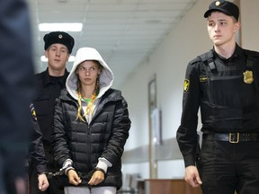 Anastasia Vashukevich, also known on social media as Nastya Rybka, center, is escorted in the court room in Moscow, Russia, Saturday, Jan. 19, 2019. A Belarusian model who claimed last year that she had evidence of Russian interference in the election of Donald Trump as U.S. president was arrested immediately upon her arrival in Moscow on Thursday following deportation from Thailand.