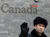 A guard attempts to block photos from being taken outside the Canadian embassy in Beijing on Jan. 27, 2019.