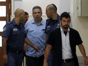 In this Thursday July 5, 2018 file photo, former Israeli cabinet minister indicted on suspicion of spying for Iran, Gonen Segev, centre, is escorted by prison guards as he arrives at court in Jerusalem, Israel. Segev will serve 11 years in prison as part of a plea bargain with authorities, Israel's justice ministry said Wednesday.