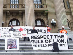 Supporters stand on the steps of the Alberta legislature during a pro-pipeline rally in Edmonton.