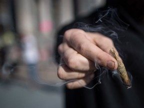 A person holds a joint while smoking marijuana to celebrate the legalization of recreational cannabis, in Vancouver, on Wednesday October 17, 2018.