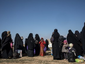 Civilians who have fled fighting in Bagouz wait to board trucks after being screened by members of the Syrian Democratic Forces (SDF) at a makeshift screening point in the desert on February 9, 2019 in Bagouz, Syria.