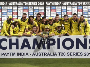 Members of Australian team pose with the winners trophy after their win in the second T20 international cricket match against India in Bangalore, India, Wednesday, Feb. 27, 2019.