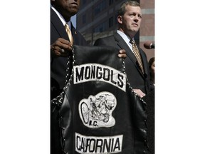 FILE - In this Tuesday, Oct. 21, 2008 file photo, U.S. Attorney Thomas P. O'Brien, right, speaks during a news conference in Los Angeles about the arrest of several Mongol motorcycle gang members in six states, as a vest with the Mongols logo is displayed. A California federal judge has refused to order the Mongols motorcycle gang to forfeit its trademarked logo, delivering a blow to prosecutors. U.S. District Court Judge David O. Carter said Thursday, Feb. 28, 2019, that such an order would have been unconstitutional.