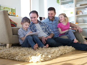 A male gay couple helps their children with homework. A new study has found that children parented by same-sex couples tend to do better in school than children of heterosexual couples.