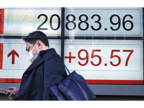 A man walks past an electronic stock board showing Japan's Nikkei 225 index at a securities firm in Tokyo Monday, Feb. 4, 2019. Asian markets were mixed Monday as traders questioned an imminent meeting between American and Chinese officials to work on disagreements ranging from technology development to trade.