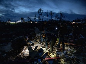 Family and friends of David Wayne Dean, who died when a tornado destroyed his house, sift through the rubble by flashlight at dusk to help his wife look for personal mementos in Beauregard, Ala., Monday, March 4, 2019.