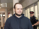 Joshua Boyle is escorted to speak to reporters at Toronto's Pearson International Airport on Oct. 13, 2017.
