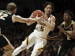 Minnesota's guard Amir Coffey controls the ball through the defense of Purdue's Evan Boudreaux and Eric Hunter Jr. during the first half of an NCAA basketball game Tuesday, March 5, 2019, in Minneapolis.