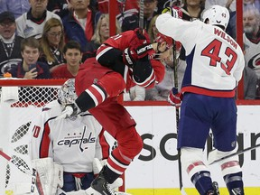 Carolina Hurricanes' Nino Niederreiter (21) tries to score on Washington Capitals goalie Braden Holtby as Capitals' Tom Wilson (43) defends during the first period of an NHL hockey game in Raleigh, N.C., Thursday, March 28, 2019.