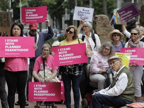 FILE - In this July 10, 2018 file photo, protesters hold signs supporting Planned Parenthood in Seattle, as they demonstrate against President Donald Trump and his choice of federal appeals Judge Brett Kavanaugh as his second nominee to the Supreme Court. On Tuesday, March 5, 2019, the American Medical Association and Planned Parenthood jointly filed a federal court lawsuit challenging a new Trump administration rule for family-planning grants which had been sought by anti-abortion activists.