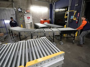 FILE - In this Nov. 9, 2018, file photo, Laurence Marzo, left, and Ty Ford, right, move a conveyor belt into place to help unload a truck carrying merchandise at a Walmart Supercenter in Houston. Ford has worked at Walmart in Houston for eight years, most recently overseeing workers tasked with unloading the trucks. On Tuesday, March 5, 2019, the Institute for Supply Management, a trade group of purchasing managers, issues its index of non-manufacturing activity for February.