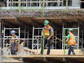 Construction workers get back on the job at the French super hospital site Tuesday, July 2, 2013 after being legislated back to work to end their two week strike in Montreal.