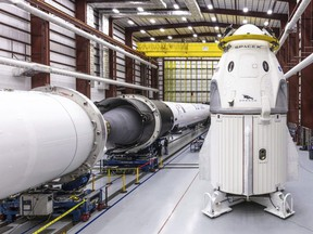 In this Dec. 18, 2018 photo provided by SpaceX, SpaceX's Crew Dragon spacecraft and Falcon 9 rocket are positioned inside the company's hangar at Launch Complex 39A at NASA's Kennedy Space Center in Florida, ahead of the Demo-1 unmanned flight test.