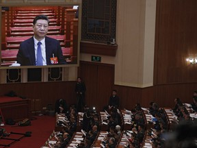 Chinese President Xi Jinping is seen on a big screen as his Premier Li Keqiang delivers the work report at the opening session of the annual National People's Congress at the Great Hall of the People in Beijing, Tuesday, March 5, 2019. China's government announced a robust annual economic growth target and a 7.5 percent rise in military spending Tuesday at a legislative session overshadowed by a tariff war with Washington.