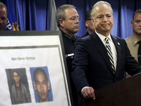 United States Attorney Nick Hanna stands next to photos of Mark Steven Domingo, during a news conference in Los Angeles on April 29, 2019.