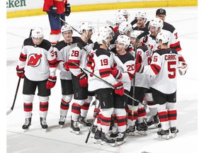 Teammates congratulate New Jersey Devils center Travis Zajac (19) after he scored the game winning goal against the Florida Panthers during the overtime period of an NHL hockey game, Saturday, April 6, 2019, in Sunrise, Fla. The Devils defeated the Panthers 4-3 in overtime.