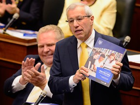Ontario Premier Doug Ford applauds as Finance Minister Vic Fedeli presents the 2019 budget in the provincial legislature in Toronto on April 11, 2019.