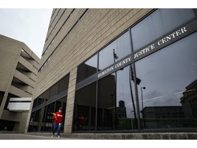 Pedestrians pass outside the Hamilton County Justice Center, Friday, April 5, 2019, in Cincinnati. A day of false hope has given way to questions about why Brian Rini would claim to be an Illinois boy who disappeared eight years ago. The FBI declared Rini's story a hoax Thursday, April 4, 2019, one day after he identified himself to authorities as Timmothy Pitzen, who disappeared in 2011 at age 6.