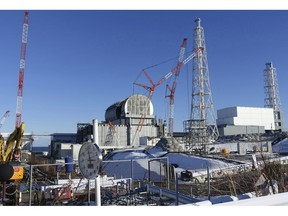 FILE - In this Jan. 25, 2018, file photo, an installation of a dome-shaped rooftop cover housing key equipment is near completion at Unit 3 reactor of the Fukushima Dai-ich nuclear power plant ahead of a fuel removal from its storage pool in Okuma, Fukushima Prefecture, northeast Japan.  Japan has partially lifted an evacuation order in one of the two hometowns of the tsunami-wrecked Fukushima nuclear plant for the first time since the 2011 disaster. The action taken Wednesday, April 10, 2019, allows people to return about 40 percent of Okuma. The other hometown, Futaba, remains off-limits as are several other towns nearby.