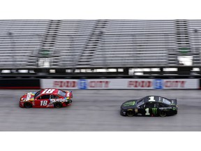 Kyle Busch (18) leads his brother Kurt Busch in the final laps of the NASCAR Cup Series auto race Sunday, April 7, 2019, at Bristol Motor Speedway in Bristol, Tenn.