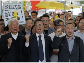 """Occupy Central leaders, from right, Benny Tai, Chan Kin Man and Chu Yiu Ming shout slogans before entering a court in Hong Kong, Tuesday, April 9, 2019. Nine leaders of the 2014 Hong Kong pro-democracy movement hear the verdicts in their trial. The co-founders of the """"Occupy Central"""" campaign - legal Professor Benny Tai Yiu-Ting, sociology professor Chan Kin-man and retired pastor Chu Yiu-ming - are facing charges related to the planning and implementation of the campaign which became part of the large-scale pro-democracy Umbrella Movement protests which were carried out 79 days between September and December 2014."""