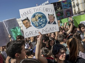 """FILE - In this March 15, 2019 file photo, a student holds a sign showing images of U.S. President Donald Trump, right, and Brazil's President Jair Bolsonaro during a protest against what the students believe are their governments' failure to take tough action against global warming, in Madrid, Spain. As a congressman and candidate, Bolsonaro often questioned the reality of climate change and cast environmental groups as foreign-influenced meddlers restraining Brazil's economic growth by holding back mining and agriculture, stances that resemble those of Trump, who before taking office described the U.S. Environmental Protection Agency as a """"disgrace"""" that largely should be dismantled."""