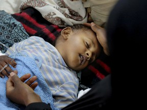 In this May 12, 2017 photo, released by UNICEF, a child is treated for suspected cholera infection at a hospital in Sanaa, Yemen. An Associated Press investigation finds that Yemen's massive cholera epidemic was aggravated by corruption and official intransigence. The investigation has found that both the Iranian-backed Houthis rebels and their main adversary in the war -- the U.S.- and Saudi-backed government that controls southern Yemen -- impeded efforts by relief groups to stem the epidemic. (UNICEF via AP)