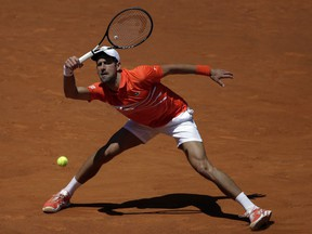 Novak Djokovic, of Serbia, returns the ball during his match against Jeremy Barty, of France, during the Madrid Open tennis tournament, in Madrid, Spain, Thursday, May 9, 2019.
