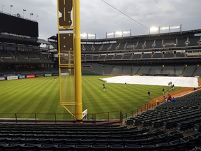 Members of the Pittsburgh Pirates warm up in the outfield of a tarp-covered Globe Life Park field as light rain showers pass through before a baseball game against the Texas Rangers in Arlington, Texas, Tuesday, April 30, 2019.