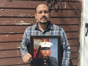 In this April 13, 2019, photo provided by the ACLU of Minnesota, Mark Esqueda poses for a portrait with a photo of him as a U.S.Marine, in Heron Lake, Minn. Esqueda was born in the United States but has been twice denied his request for a passport. He sued the State Department and is asking a federal judge to declare that he is a U.S. citizen.