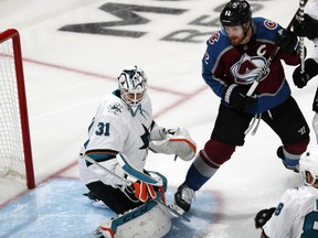 San Jose Sharks goaltender Martin Jones, left, stops a shot by Colorado Avalanche left wing Gabriel Landeskog during the first period of Game 3 of an NHL hockey second-round playoff series Tuesday, April 30, 2019, in Denver.