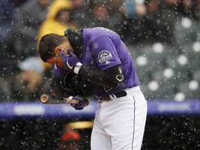 Colorado Rockies' Nolan Arenado cleans snow out of his ear while batting against the San Francisco Giants in the first inning of a baseball game Thursday, May 9, 2019, in Denver.