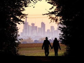 A couple walks through a forest with the Frankfurt skyline in background near Frankfurt, Germany, Oct. 21, 2018. Development that's led to loss of habitat, climate change, overfishing, pollution and invasive species is causing a biodiversity crisis, scientists say in a new United Nations science report released Monday, May 6, 2019.