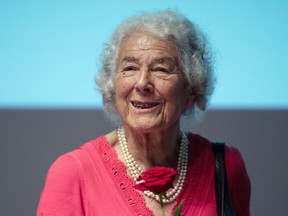 """FILE - In this Sept. 15, 2016 file photo British writer Judith Kerr holds a rose in Berlin, Germany. Judith Kerr, author and illustrator of the bestselling """"The Tiger Who Came to Tea"""" and other beloved children's books, has died at the age of 95."""
