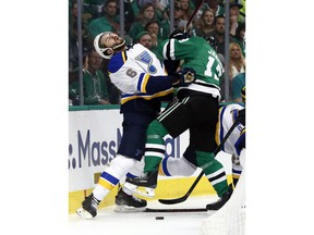 St. Louis Blues' Joel Edmundson (6) recoils after being hit by Dallas Stars' Mattias Janmark, of Sweden, while fighting for control of a loose puck along the boards during the first period in Game 6 of an NHL second-round hockey playoff series, Sunday, May 5, 2019, in Dallas.