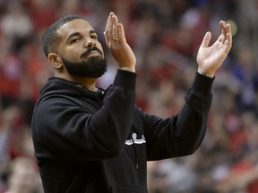 """Toronto-born performer Aubrey """"Drake"""" Graham cheers from courtside during first half NBA Eastern Conference finals action between the Toronto Raptors and the Milwaukee Bucks, in Toronto on Saturday, May 25, 2019."""